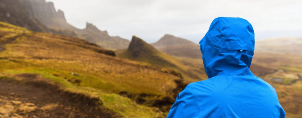 Canva - Man in rain jacket at Quiraing, Isle of Skye