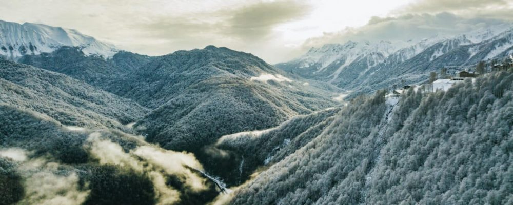 aerial winter snowy mountain trees forest with cloudy sky